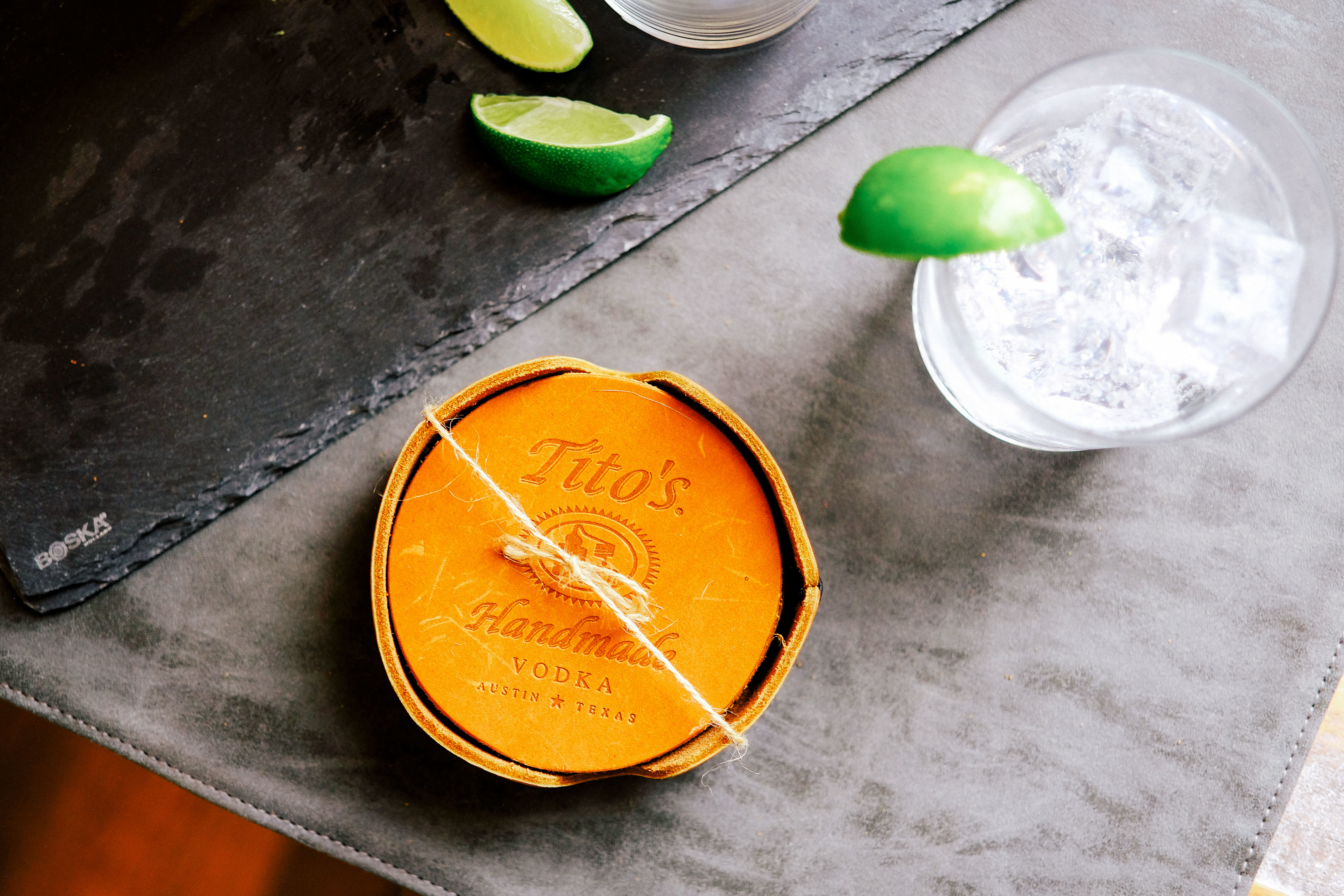 Tito's Leather Coaster Collection on a table with a cocktail