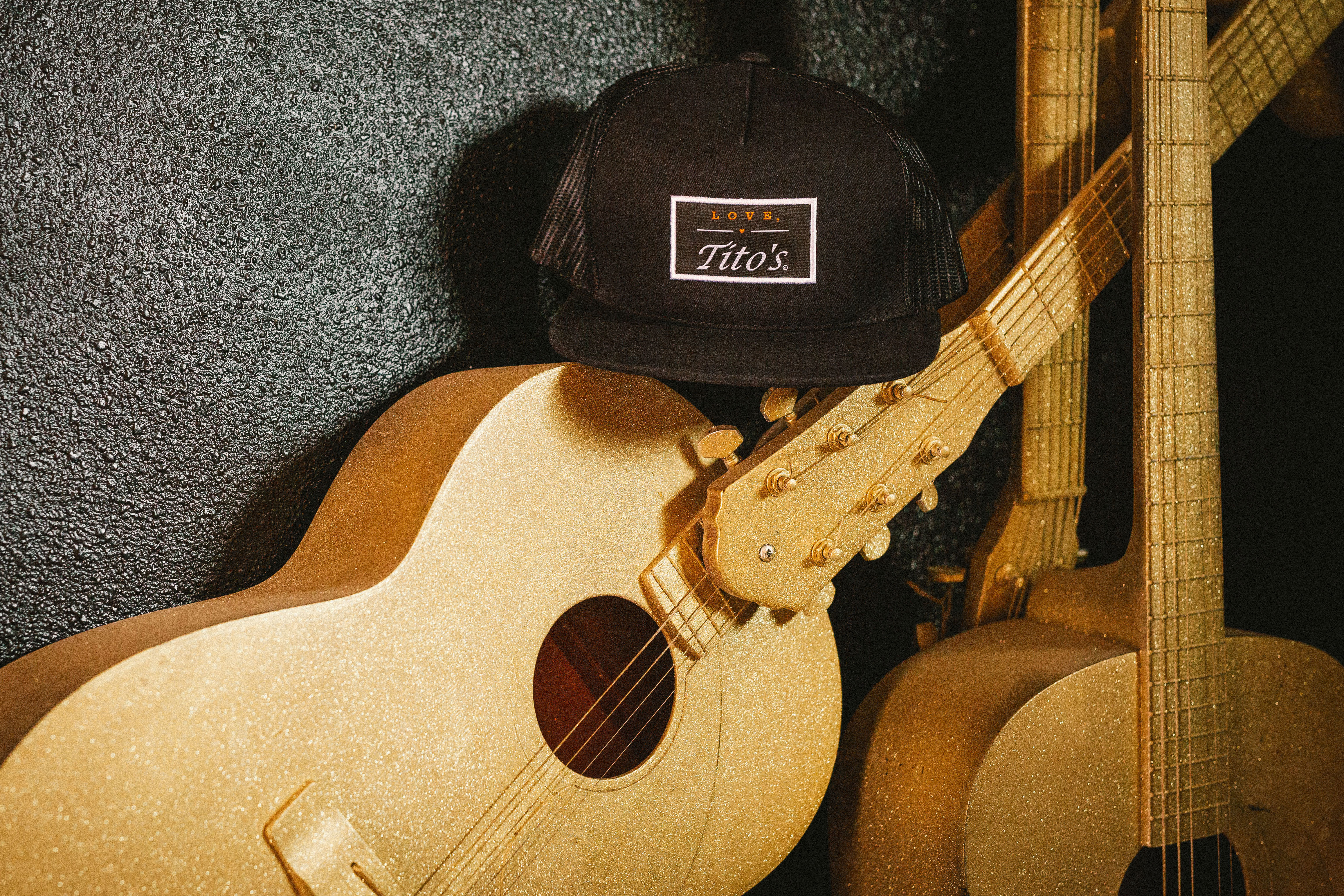 Love, Tito's Patch Hat sitting on copper painted guitars