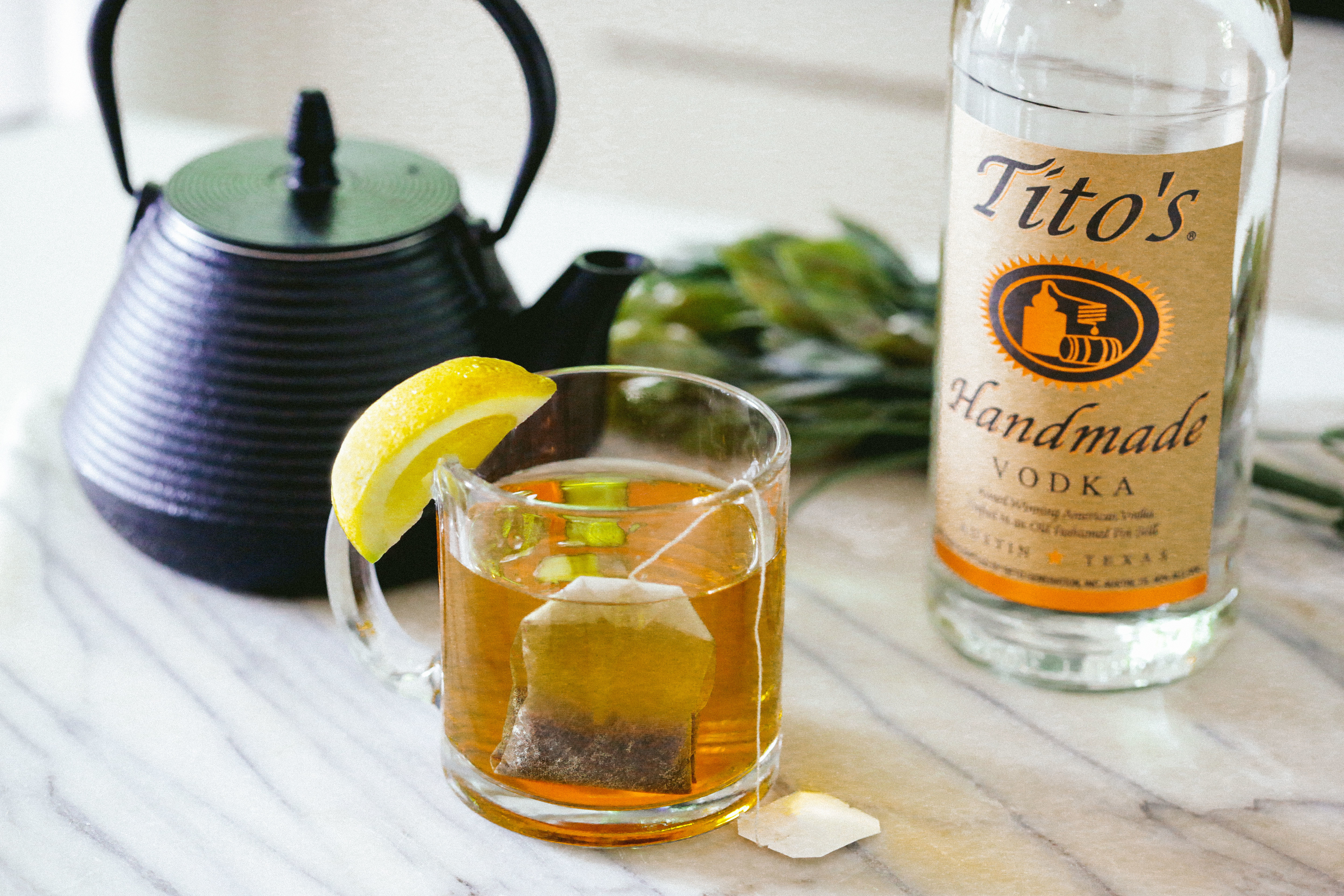 Tito's Toddy in a glass mug with a lemon garnish, a tea kettle and bottle of Tito's Handmade Vodka in the background