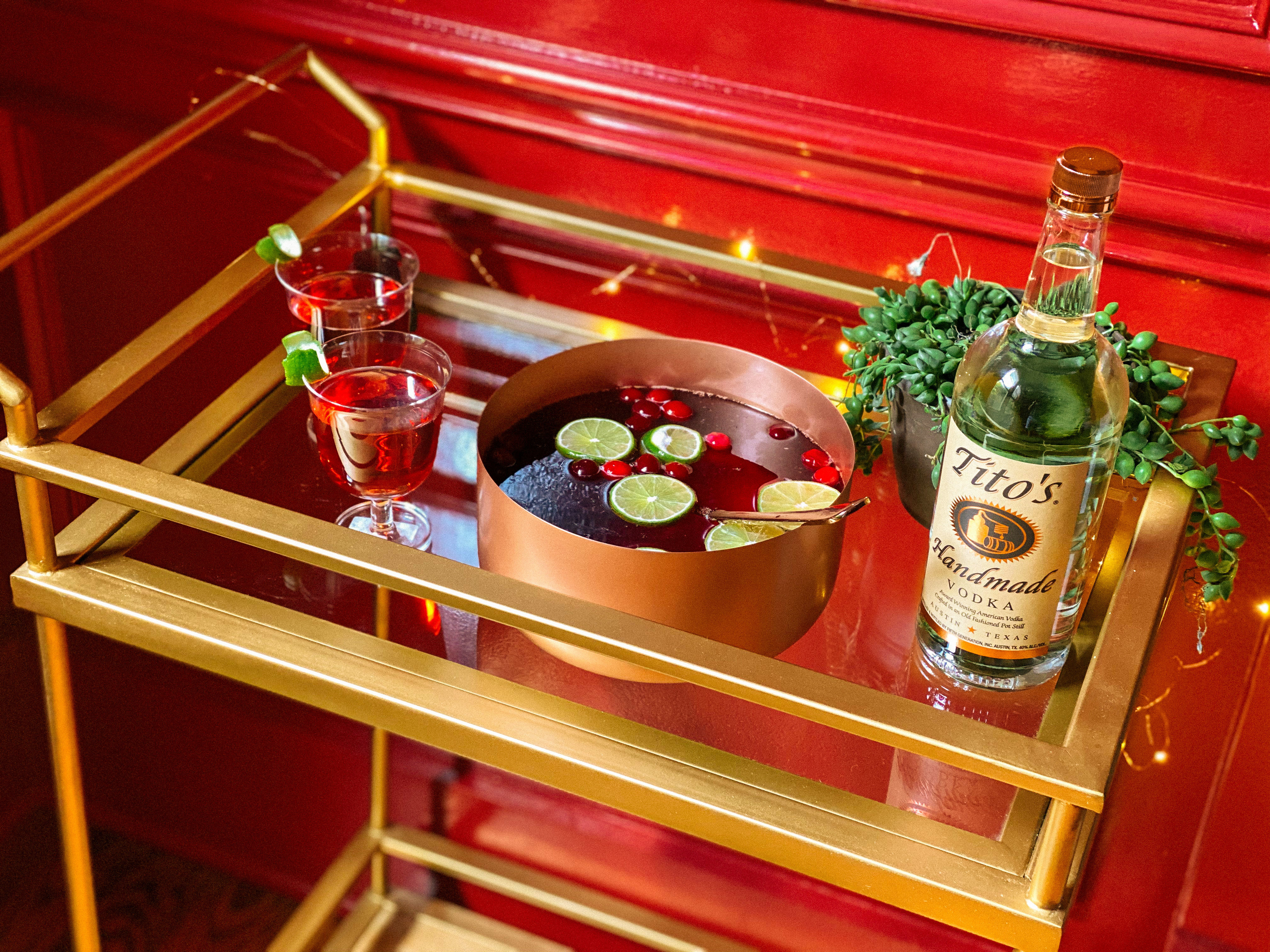 Tito's Tropical Holiday Punch in a pot on a bar cart with two glasses and a bottle of Tito's Handmade Vodka