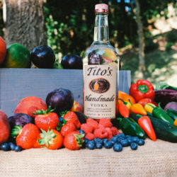 TIto's Vodka bottle in the middle of colorful fruits and vegetables