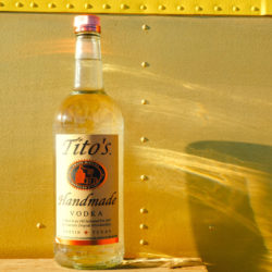 Tito's Vodka bottle in front of yellow background