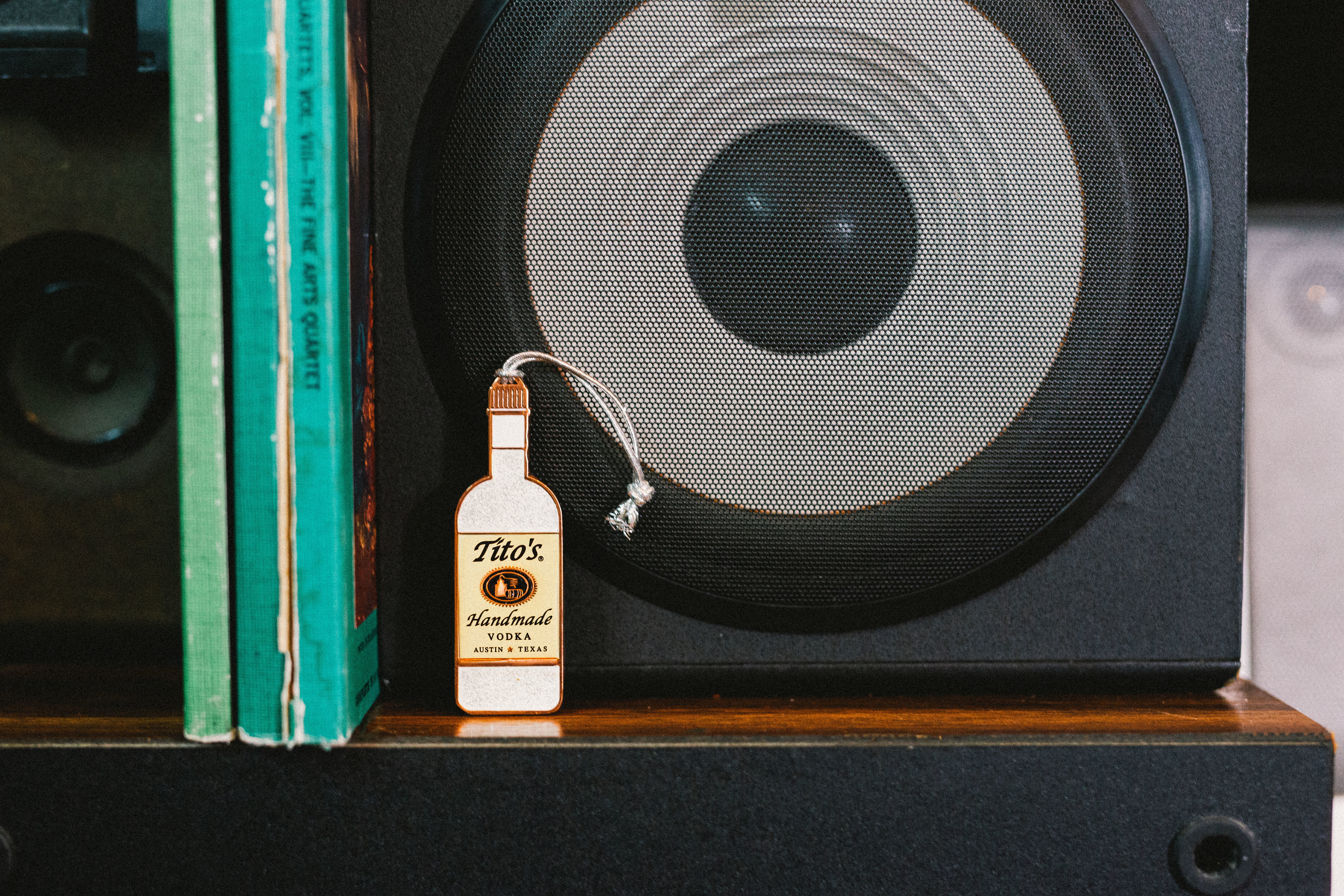 Tito's Stardust Sparkle Bottle Ornament on a bookshelf in front of a speaker