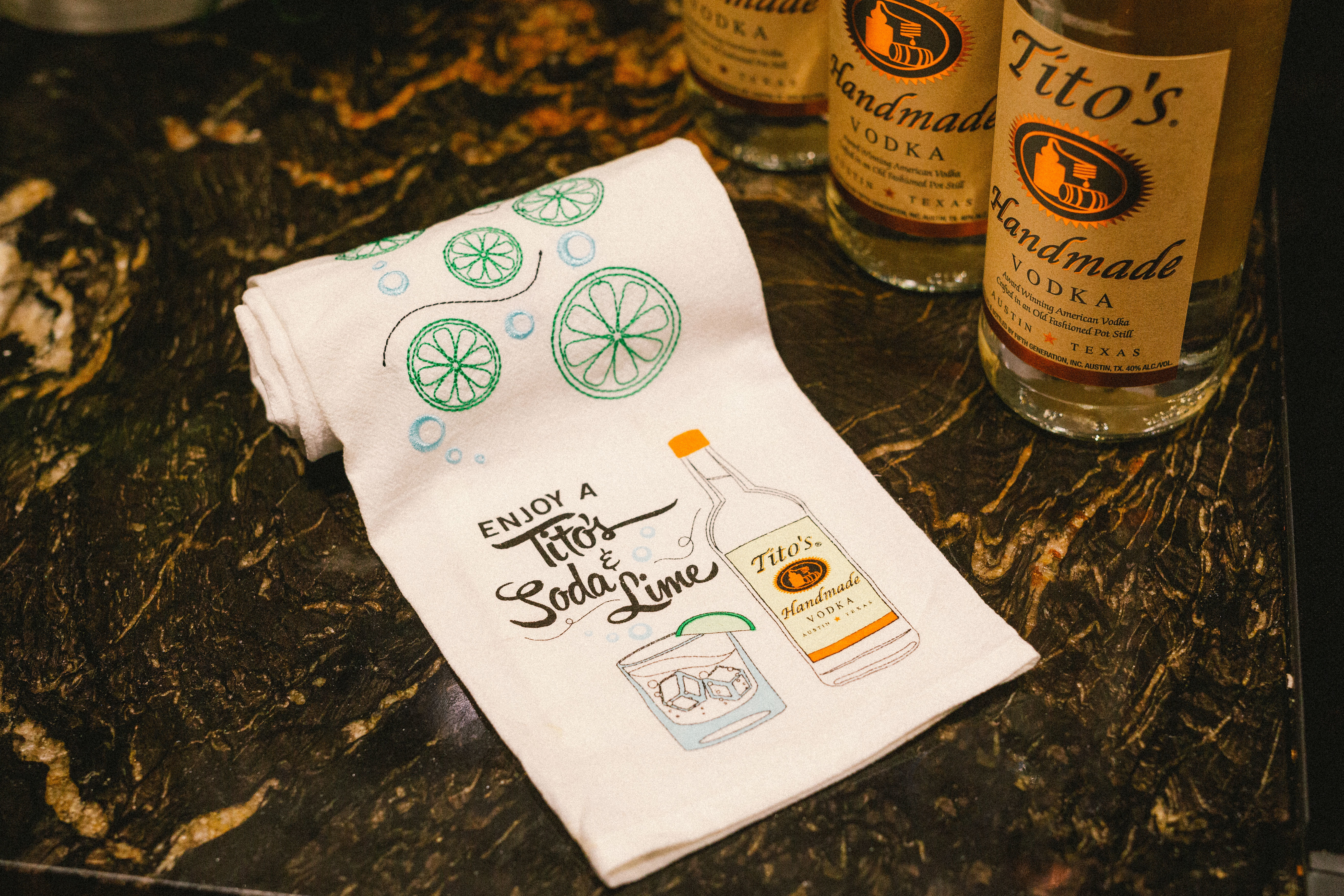 White tea towel with printed Enjoy a Tito's Soda & Lime design and embroidered limes next to bottles of Tito's Vodka