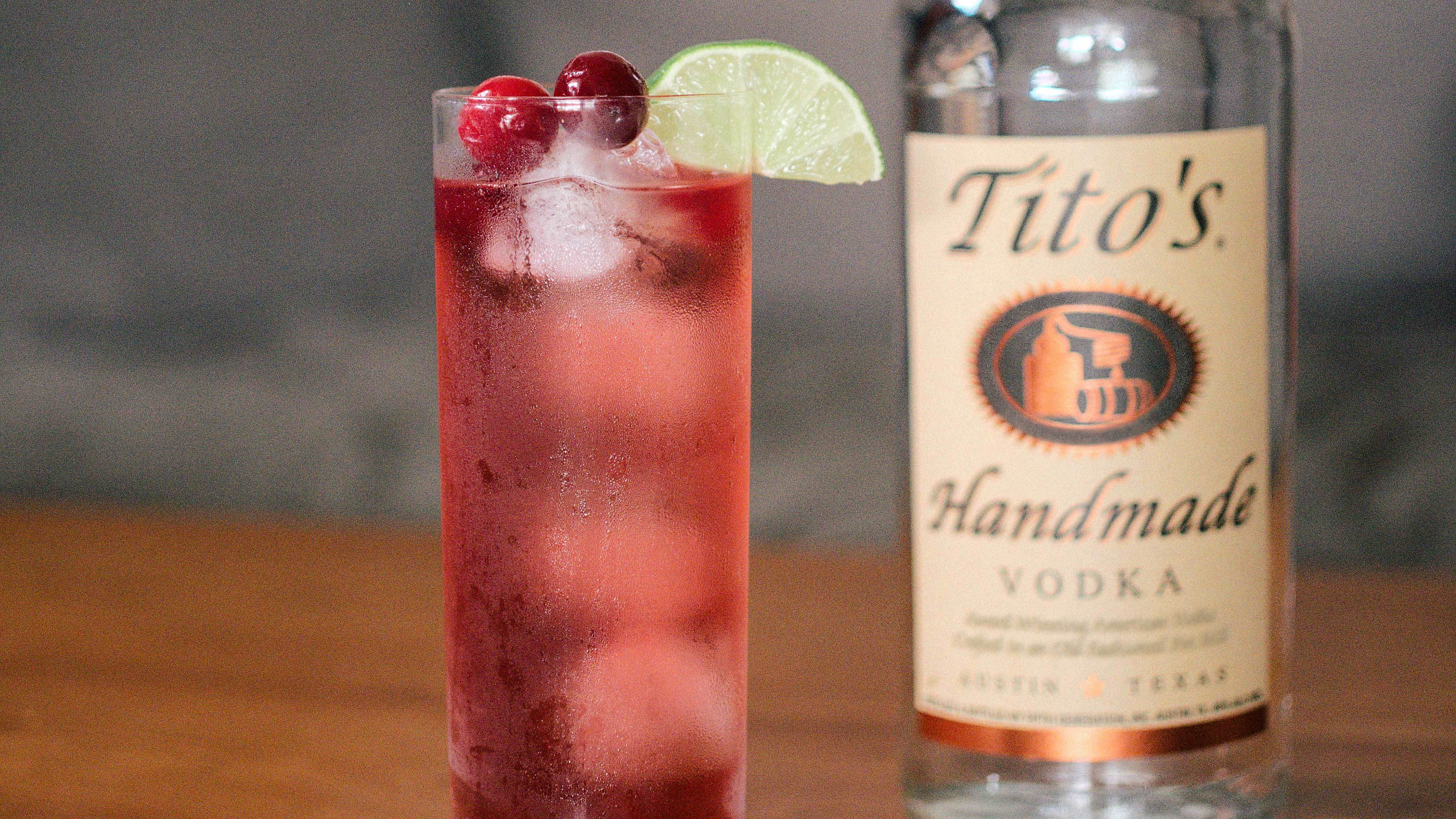 Tito's & Cranberry garnished with a lime slice and two cranberries