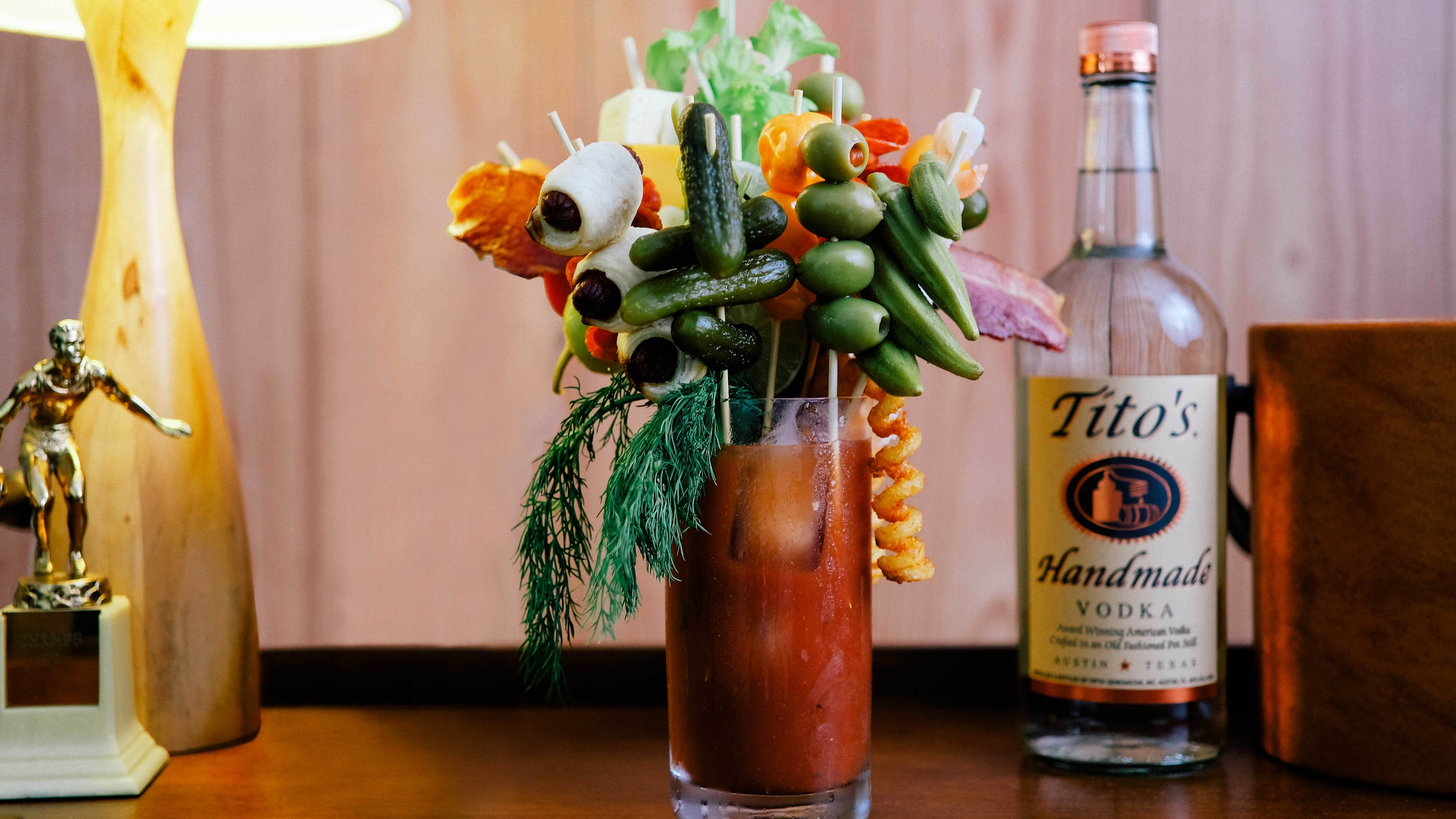 Tito's Bloody Mary loaded with garnishes including french fries, olives, pickles, bacon, onions, celery