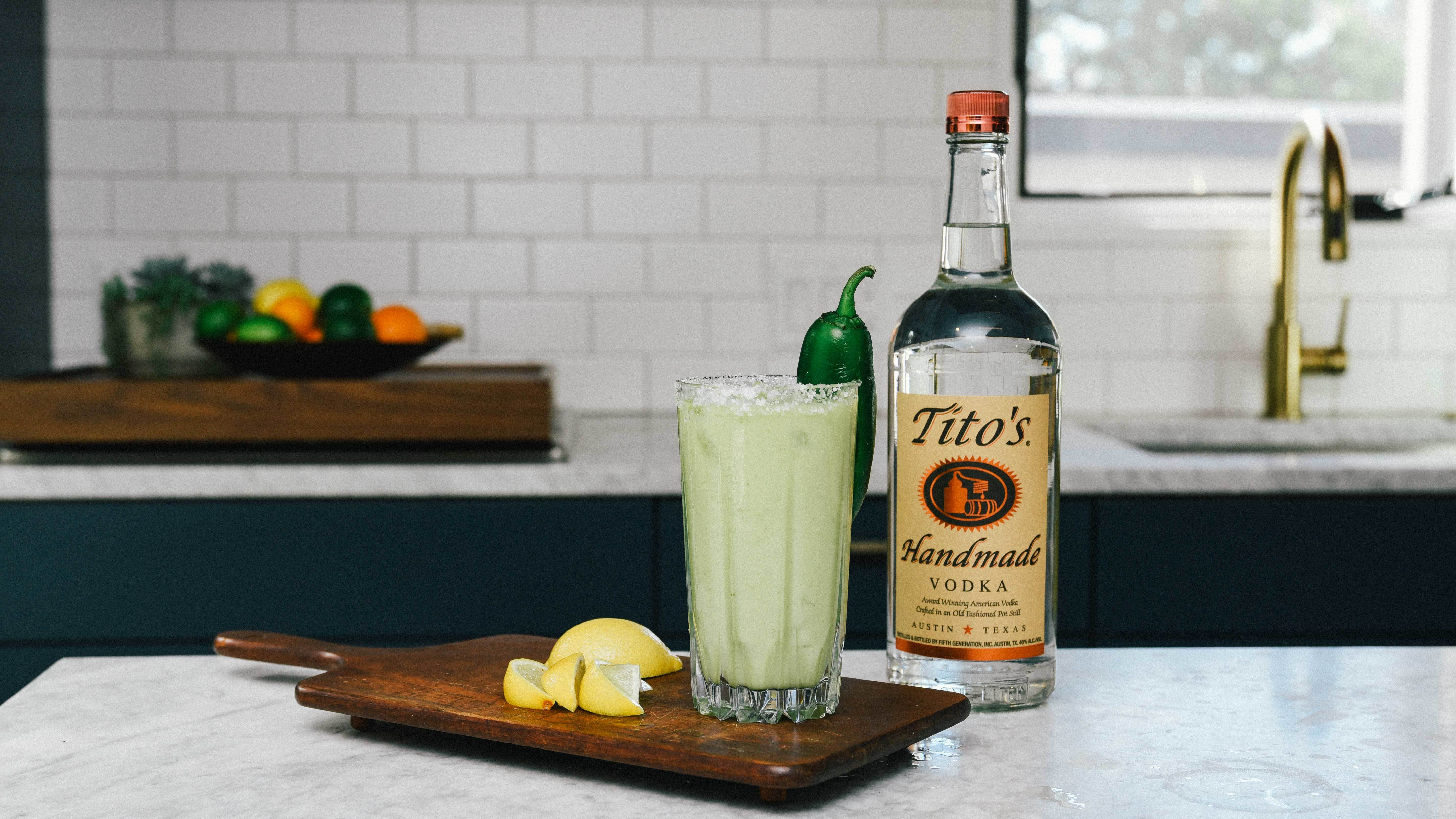 Tito's Blooming Mary garnished with a jalapeño next to a Tito's Vodka bottle