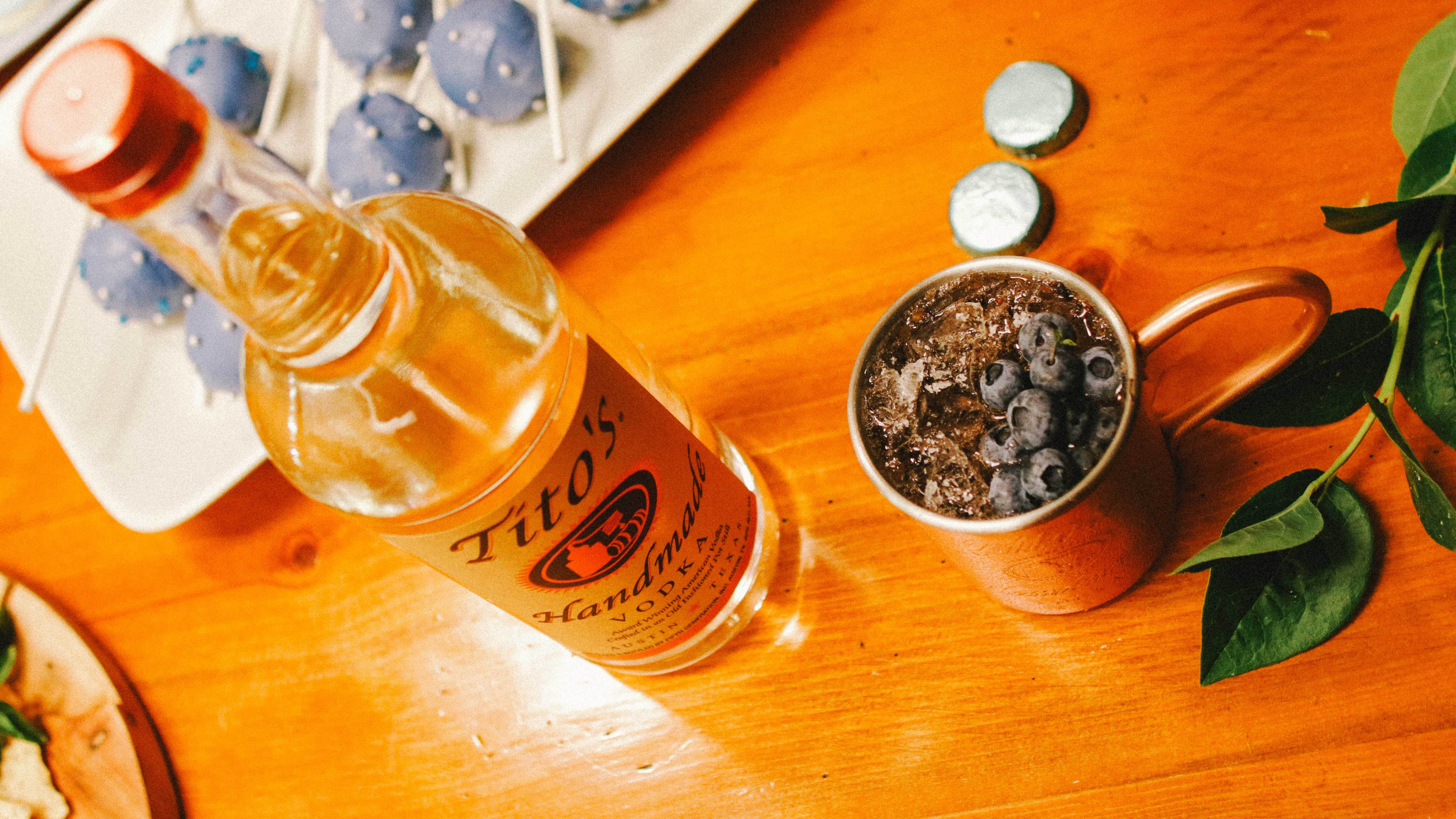 Tito's Vodka bottle next to a Blueberry Mule in a copper Mug garnished with blueberries