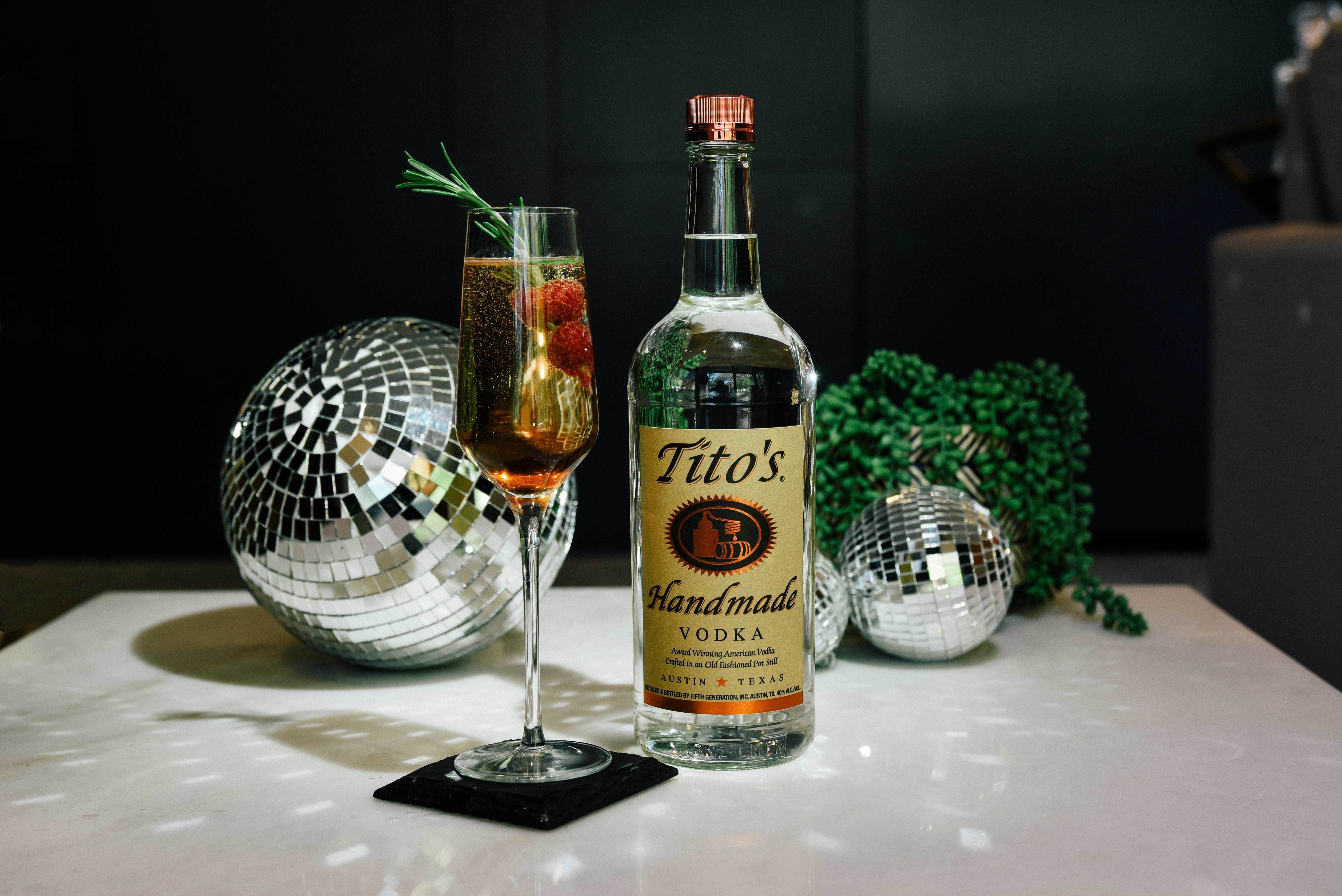 Tito's Berry Dazzler next to a Tito's Vodka bottle with disco balls in the background