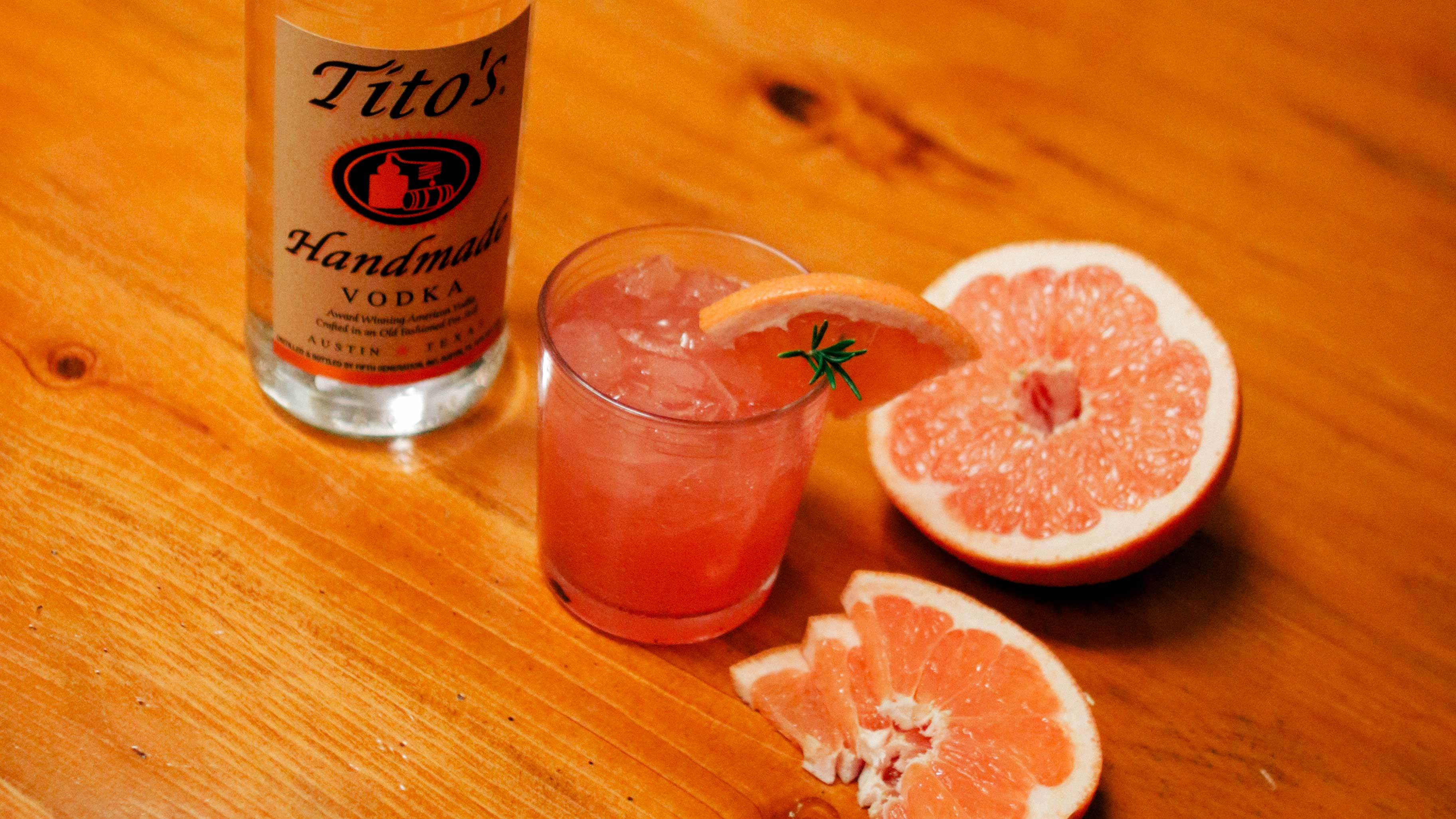 Tito's Vodka bottle next to a Tito's Greyhound garnished with a grapefruit slice