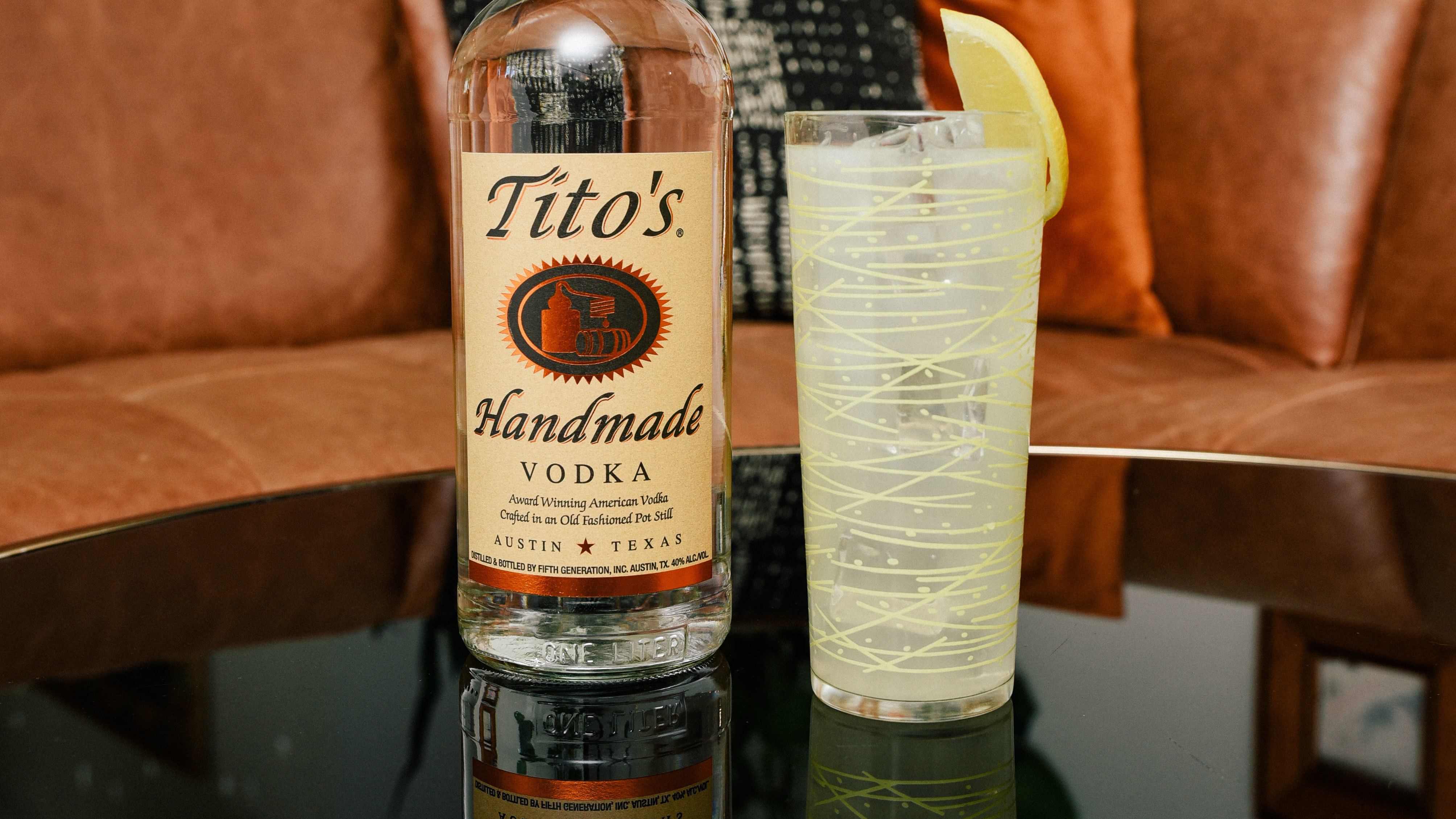 Tito's bottle next to Tito's Lemonade a tall class
