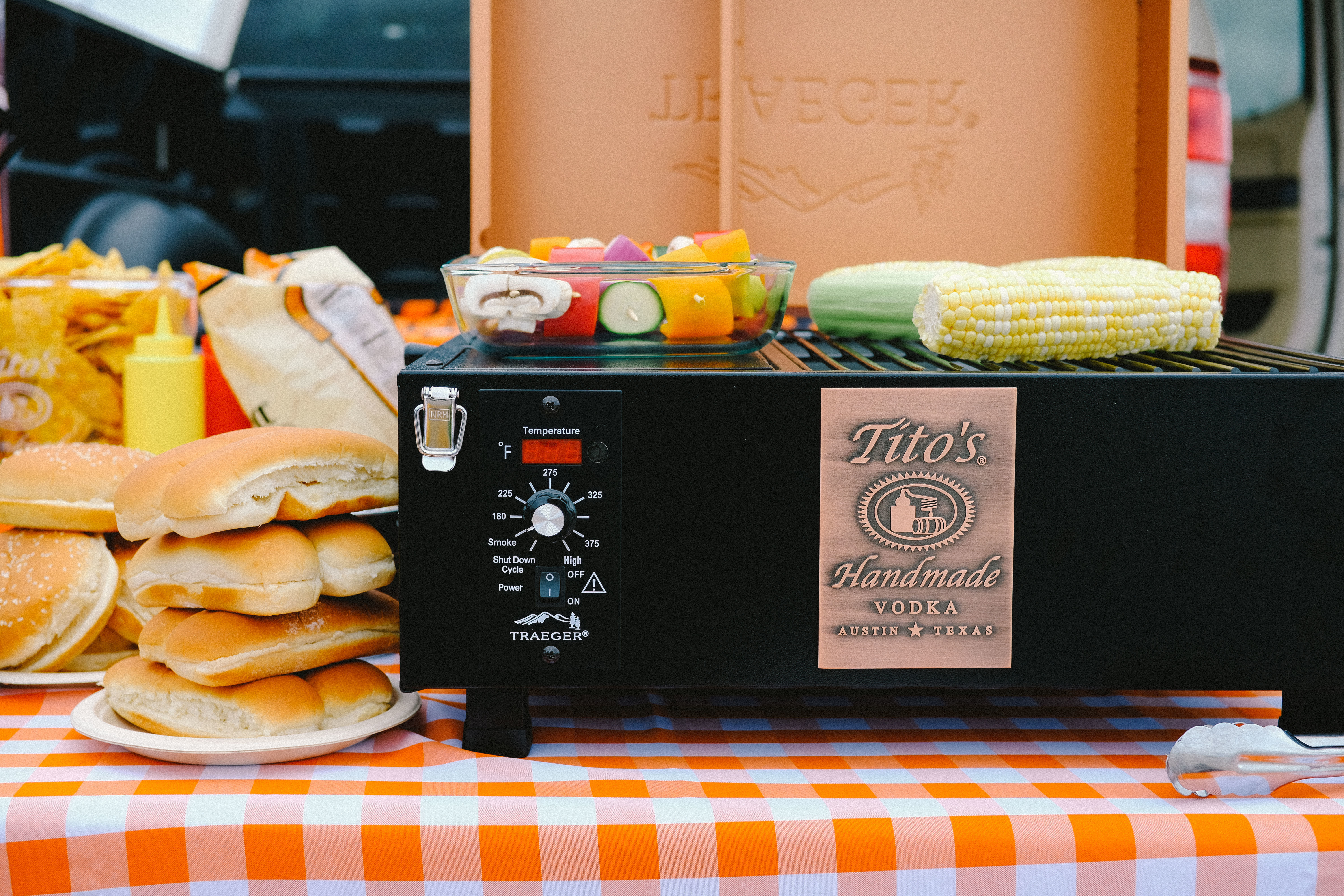 Tito's custom PTG Traeger Grill with vegetables and hot dog buns