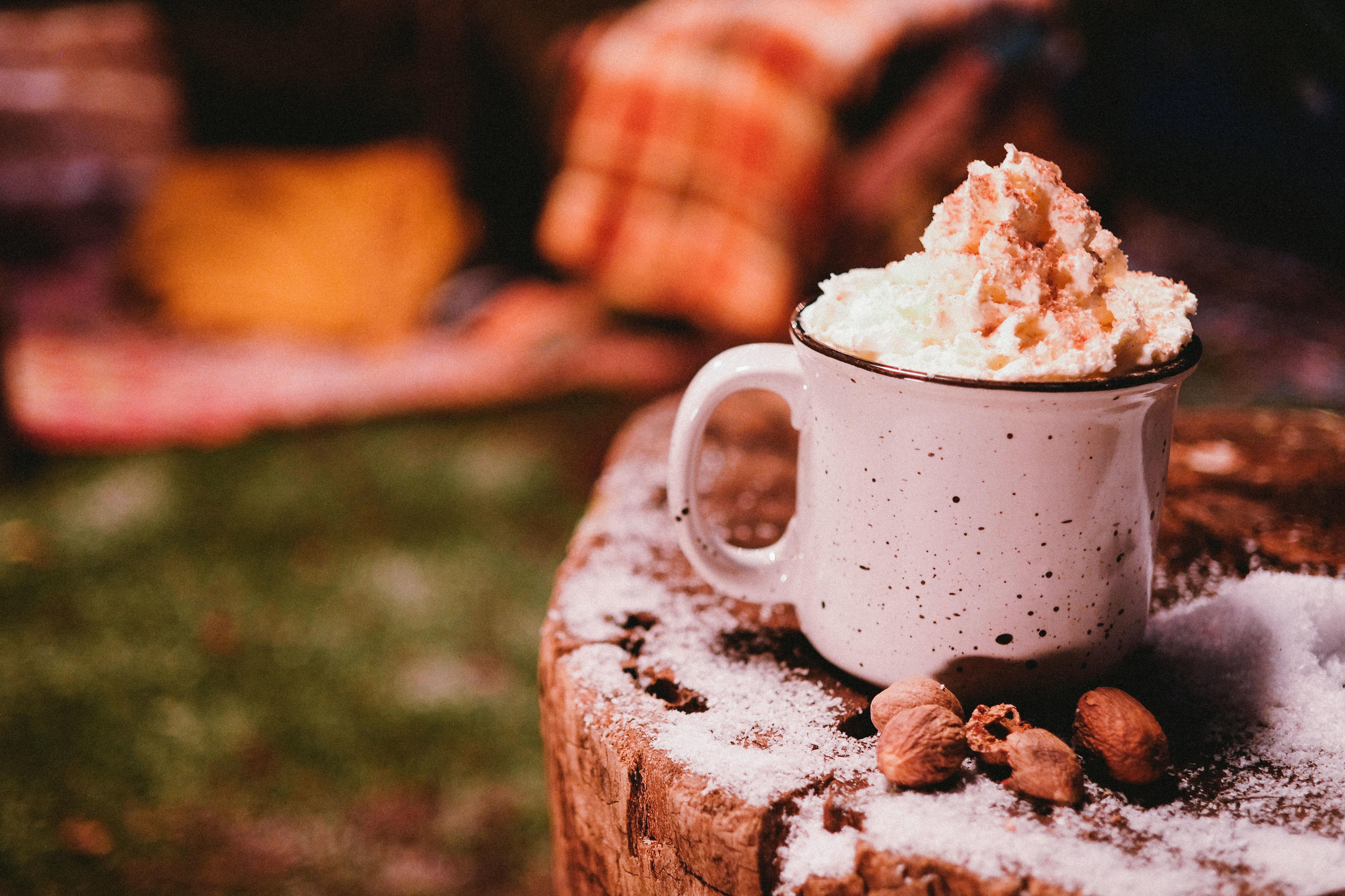 Cocktail in a mug topped with whipped cream sitting on a tree stump