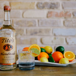 Tito's All-Time Favorite garnished with orange and lime wedges in front of a plate of limes, lemons, and oranges, next to a bottle of Tito's Vodka
