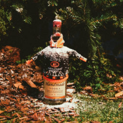 Tito's Vodka bottle in a holiday sweater sitting on grass, leaves, and snow