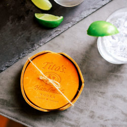 Tito's Leather Coaster set on a table with a cocktail
