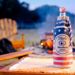 Tito's Vodka bottle in a Red, White & Blue bottle bag with campfire in background