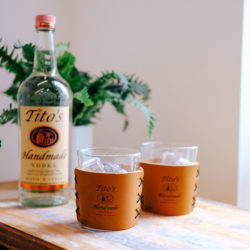Leather Highball Set with Tito's Handmade Vodka logo on a table with a bottle of Tito's
