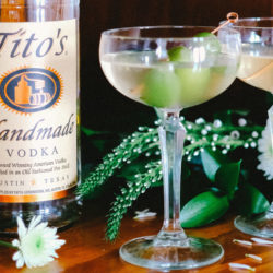 Two Olive You So Much cocktails on a table with white flowers and a Tito's Vodka bottle