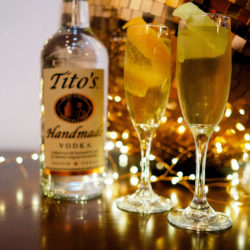 Tito's Handmade Vodka bottle with two champagne flutes, copper disco ball, and lights on table