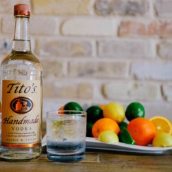 Tito's Vodka bottle next to a Tito's & Tonic cocktail with a plate of citrus fruits