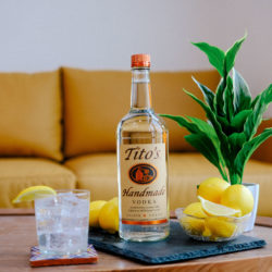 A bottle of Tito's Handmade Vodka on a table with a bowl of lemons and a Tito's Water & Lemon cocktail