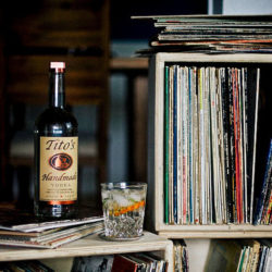Bottle of Tito's Vodka and a cocktail in a room of vinyl records