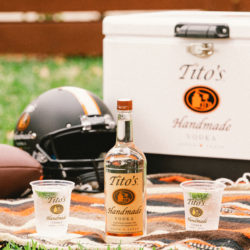 Tito's Vodka bottle with two cocktails and cooler with a football and helmut