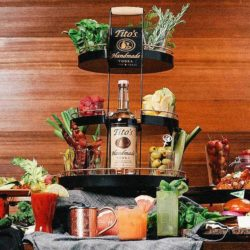Tito's Home Bar Server stocked with garnishes surrounded by snacks and cocktails