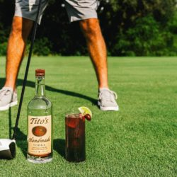 Tito's Vodka bottle and cocktail on a golf course