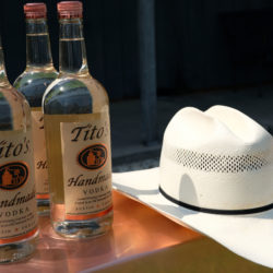 Tito's Handmade Vodka bottles sitting on a bar with a cowboy hat.