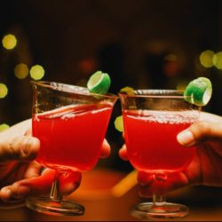 Two hands cheersing with cocktails