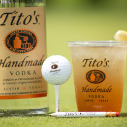 Tito's bottle, golf ball on a tee, and a Tito's Lemonade and Tea on a golf course