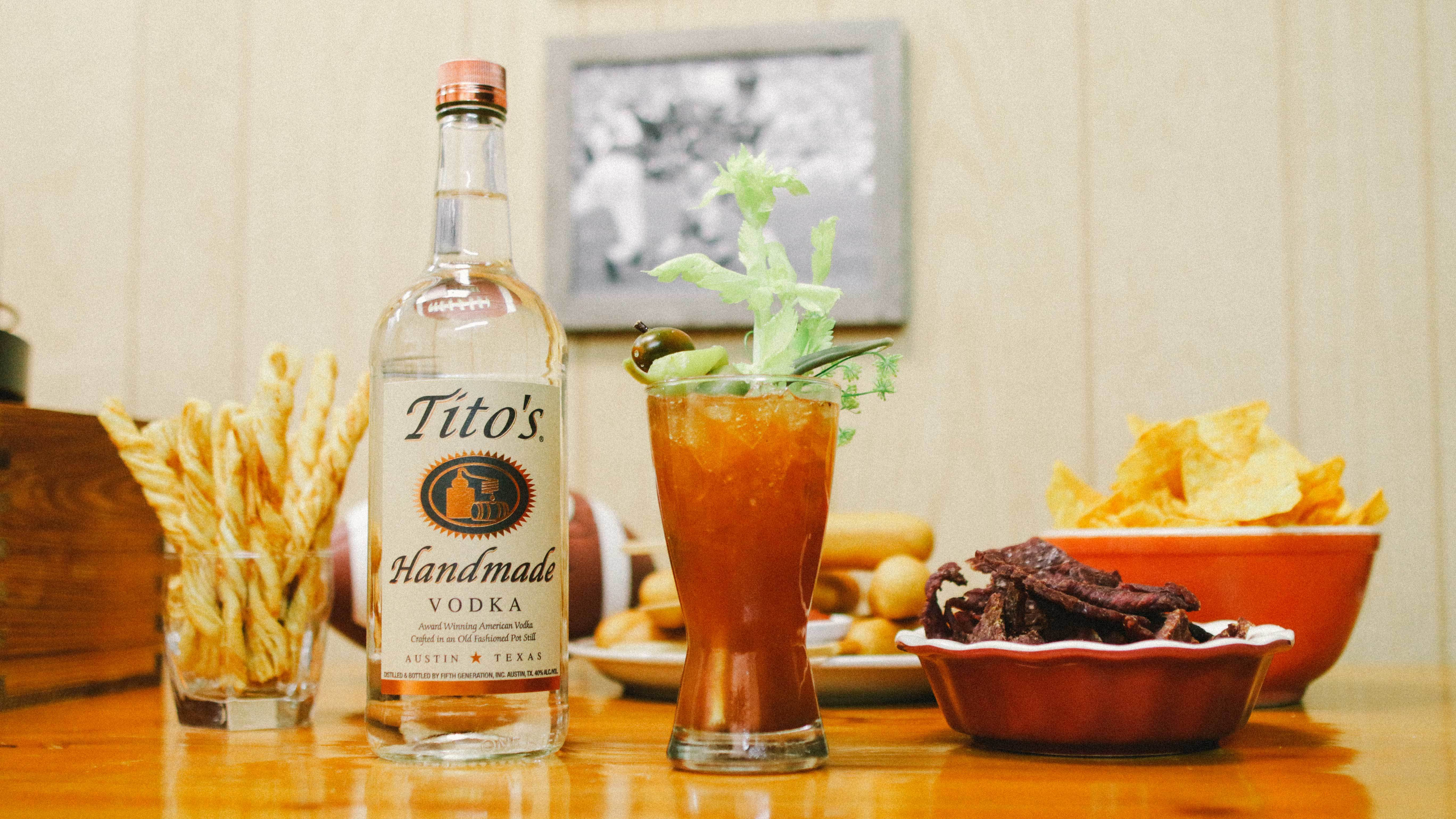 Tito's Bloody Mary on a table with a Tito's Vodka bottle and bowls of snacks
