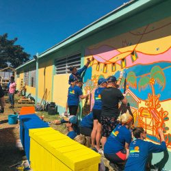 Volunteers working on a wall mural in the Bahamas